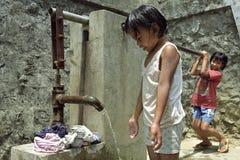 Vêtements philippins de lavage de filles à la pompe à eau Photographie stock libre de droits