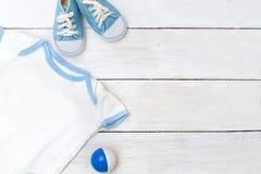 Vêtements pour l'enfant et les chaussures sur un fond en bois blanc Images libres de droits