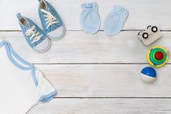 Vêtements pour l'enfant et les jouets d'enfants sur un fond en bois blanc Photos libres de droits