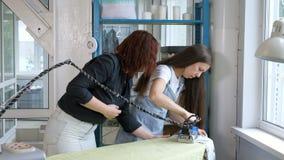 Vêtements repassants d'ouvrière couturière avec la vapeur, fer de enseignement de femme dans l'atelier de tailleur clips vidéos