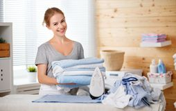 Vêtements repassants de femme au foyer heureuse de femme dans la blanchisserie à la maison photos stock