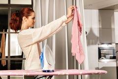 Vêtements repassants de jeune belle femme rousse photographie stock libre de droits