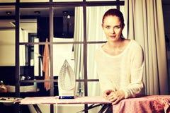 Vêtements repassants de jeune belle femme rousse photos libres de droits