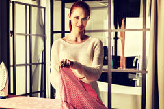 Vêtements repassants de jeune belle femme rousse photo stock
