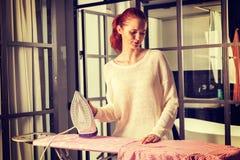 Vêtements repassants de jeune belle femme rousse images libres de droits