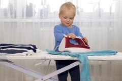 Vêtements repassants de sourire heureux de garçon Enfant aidant avec les travaux domestiques Autonomie d'une manière encourageant photos stock