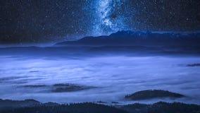 Vía láctea sobre las nubes que fluyen en las montañas en la noche, Polonia de Tatra metrajes