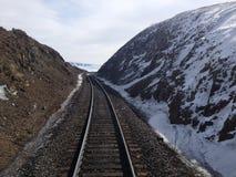 Vías del tren en las montañas nevosas Imagenes de archivo