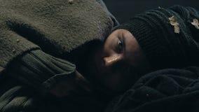 Víctima de la guerra que calienta debajo de la manta, ocultando en refugio de bomba, esperanza de la salvación almacen de video