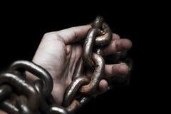 Víctima, esclavo, manos masculinas del prosoner atadas por la cadena grande del metal por hola foto de archivo libre de regalías