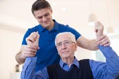 Víctima masculina de Assessing Senior Stroke de la enfermera aumentando los brazos fotos de archivo