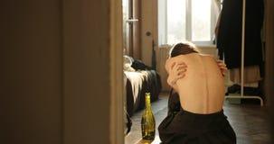 Víctima y concepto de la enfermedad La mujer joven gritadora se rasguña que se sienta en el piso en el cuarto y que llora, bebien almacen de metraje de vídeo