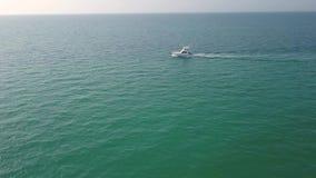 Vídeo aéreo com o zangão sobre o mar e a praia com barcos e iate