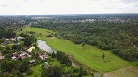 Vídeo aéreo da opinião 4K UHD de opinião superior do zangão de Letónia da vila das casas de campo do prado do rio de Gauja video estoque