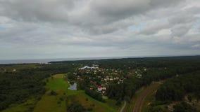 Vídeo aéreo da opinião 4K UHD de opinião superior do zangão de Letónia da vila das casas de campo do prado do rio de Gauja vídeos de arquivo