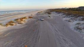 Vídeo aéreo de la conducción de automóviles en la playa almacen de metraje de vídeo