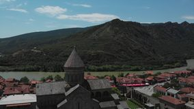 Vídeo aéreo de la iglesia antigua Sveti Tskhoveli Georgia, Mtskheta Vuelo ascendente cercano al monasterio almacen de video