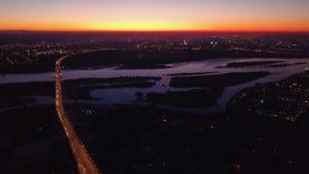 Vídeo aéreo de Novosibirsk Rusia Ciudad de la noche en la puesta del sol Puesta del sol reflejada en el río Conduzca los coches e metrajes