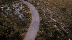 Vídeo aéreo del abejón del ciclista del camino en la puesta del sol almacen de metraje de vídeo