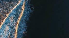 Vídeo aéreo del abejón de las olas oceánicas que se estrellan en orilla El seguimiento del tiro del mar agita creando una textura almacen de metraje de vídeo
