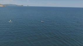 Vídeo aéreo del abejón del sorbo entre 2 hombres en aguas del Caribe tropicales metrajes