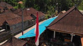 vídeo aéreo del vuelo 4K de agitar a nacional indonesio en pueblo del balinese durante la celebración grande Isla de Bali, Indone almacen de metraje de vídeo