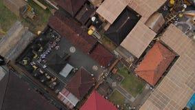 vídeo aéreo del vuelo 4K de las casas del balinese durante la celebración grande Ceremonia de Bali en el pueblo, Ubud Tejados del almacen de metraje de vídeo