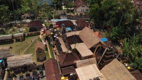 vídeo aéreo del vuelo 4K de las casas del balinese durante la celebración grande Ceremonia de Bali en el pueblo, Ubud Tejados del metrajes