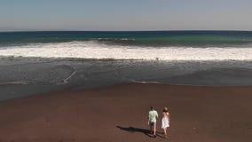 vídeo aéreo do voo 4K de pares novos na praia com a areia vulcânica preta no tempo do por do sol Ilha de Bali filme