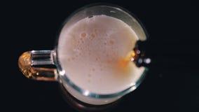 Vídeo acelerado de la cerveza de relleno de una botella de una taza de cerveza grande Primer muy bonito en el top con la acelerac metrajes