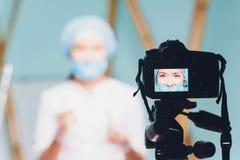 Vídeo bonito alegre do vlog da gravação do doutor da mulher sobre a medicina e os cuidados médicos imagens de stock royalty free