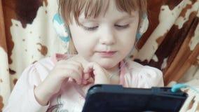 Vídeo bonito pequeno do relógio da menina na tabuleta digital vídeos de arquivo