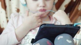 Vídeo bonito pequeno do relógio da menina na tabuleta digital filme