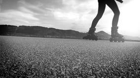 Vídeo a cámara lenta blanco y negro: una persona pasa encendido las rodillo-cuchillas almacen de metraje de vídeo