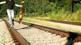 Vídeo a cámara lenta de un adolescente que camina por el ferrocarril que sostiene una guitarra metrajes