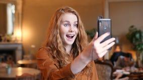 Vídeo caucásico de la tecnología del teléfono de Smart de la mujer del pelo rojo joven que llama en café metrajes