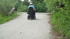 vídeo da definição 4k de um homem na cadeira de rodas elétrica que elimina a estrada na natureza vídeos de arquivo