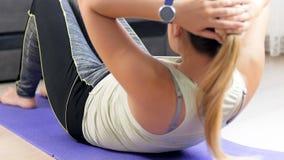 Vídeo da jovem mulher que encontra-se na esteira da ioga e que ajusta o perseguidor da aptidão em seu pulso antes de fazer tritur vídeos de arquivo