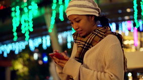 Vídeo da menina asiática que usa o telefone esperto durante a época natalícia com fundo da luz de Natal Sumário de uma comunicaçã vídeos de arquivo
