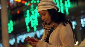 Vídeo da menina asiática que usa o telefone esperto durante a época natalícia com fundo da luz de Natal Sumário de uma comunicaçã video estoque