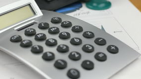 Vídeo da pena, da calculadora, do telefone celular e da bacia encontrando-se nos diagramas Tiro da zorra Close-up vídeos de arquivo