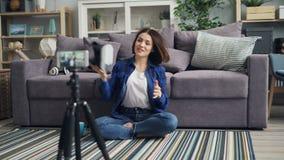 Vídeo de gravação do vlogger bonito sobre os vidros do vr que vestem o dispositivo e que falam em casa video estoque