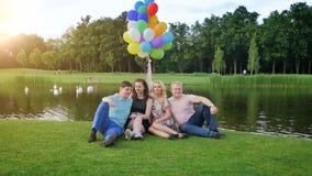 Vídeo de la cámara lenta de 4 amigos que se relajan en el riverbank en el parque almacen de video