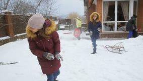 Vídeo de la cámara lenta de dos hermanas que tienen lucha de la bola de la nieve en el patio trasero almacen de video