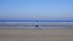 Vídeo de la cámara lenta de la mujer joven del ajuste que corre en la playa metrajes