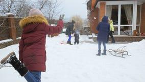 Vídeo de la cámara lenta de los niños que tienen lucha de la bola de la nieve en el patio trasero de la casa almacen de video