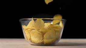 Vídeo de la cámara lenta de las patatas fritas groved que caen al bol de vidrio, patatas fritas groved, bocados para la cerveza,  almacen de metraje de vídeo