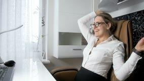Vídeo de la cámara lenta de los papeles que lanzan de la empresaria alegre en oficina y de la relajación en silla