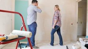 Vídeo de la cámara lenta de los pares jovenes que discuten mientras que hace la renovación en nueva casa del hteir
