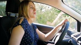 Vídeo de la cámara lenta de la mujer joven hermosa que conduce un coche y que canta con la radio Buen humor mientras que viaja en